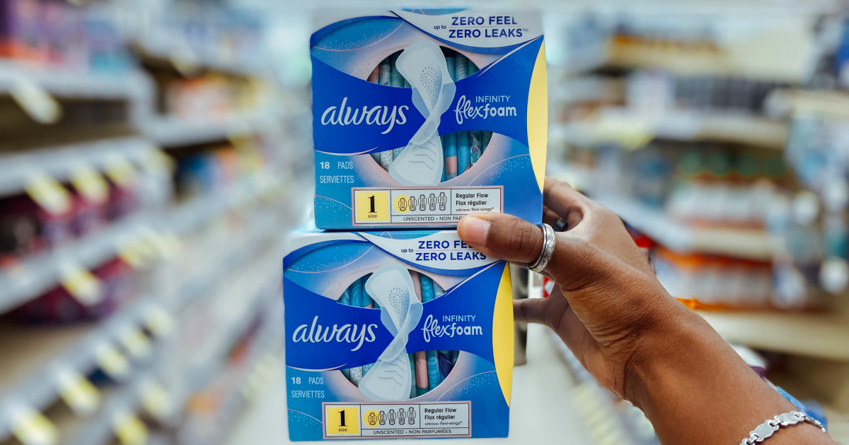hand holding up two packs of always pads in a store