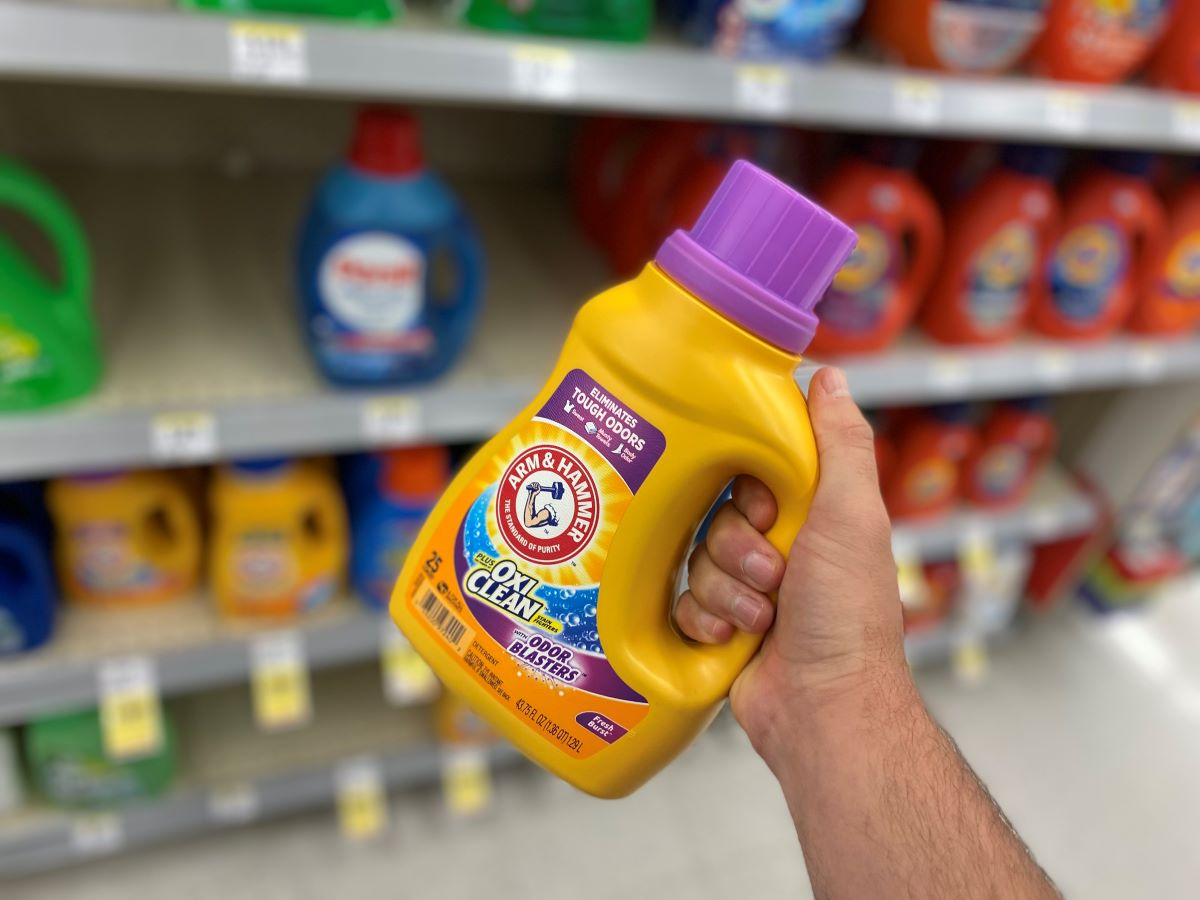 hand holding a bottle of Arm & Hammer laundry detergent