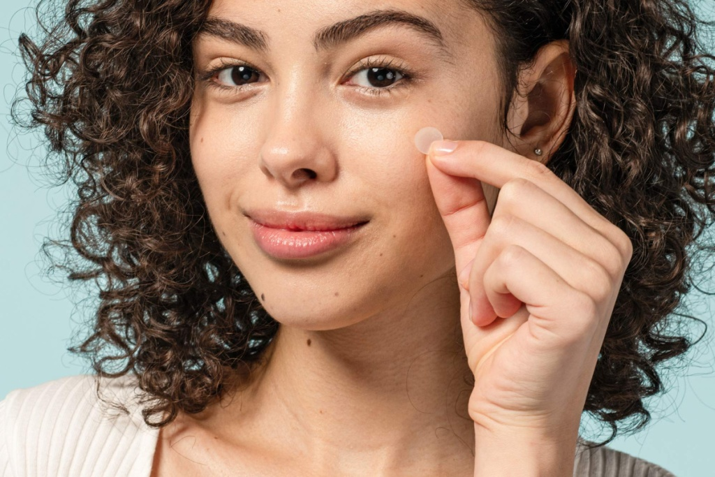 woman applying COSRX acne patches