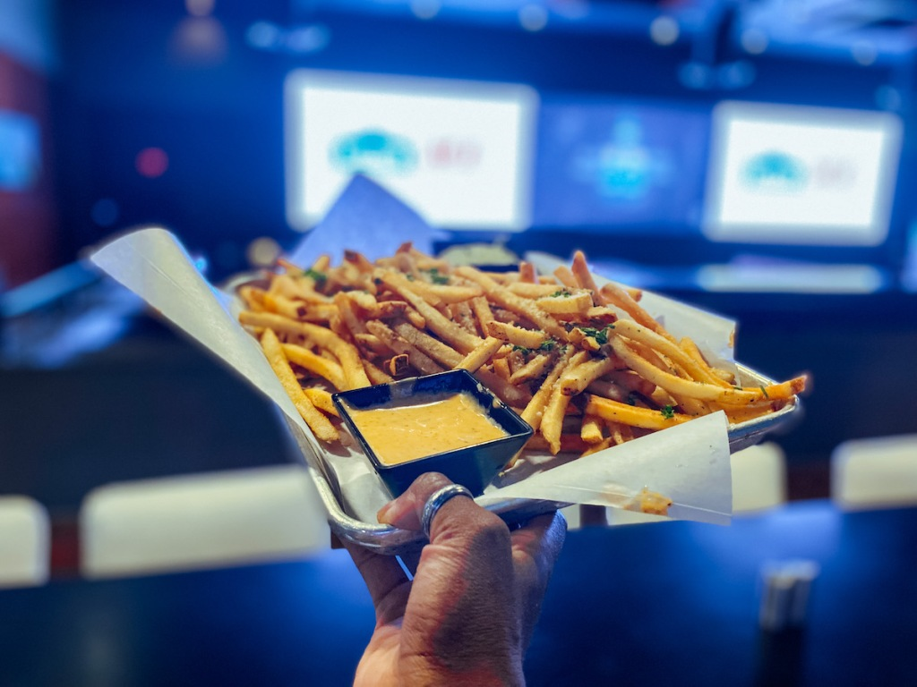 hand holding a plate of french fries in front of sports bar