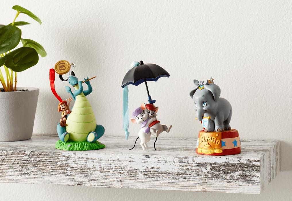 three Disney ornaments on a shelf