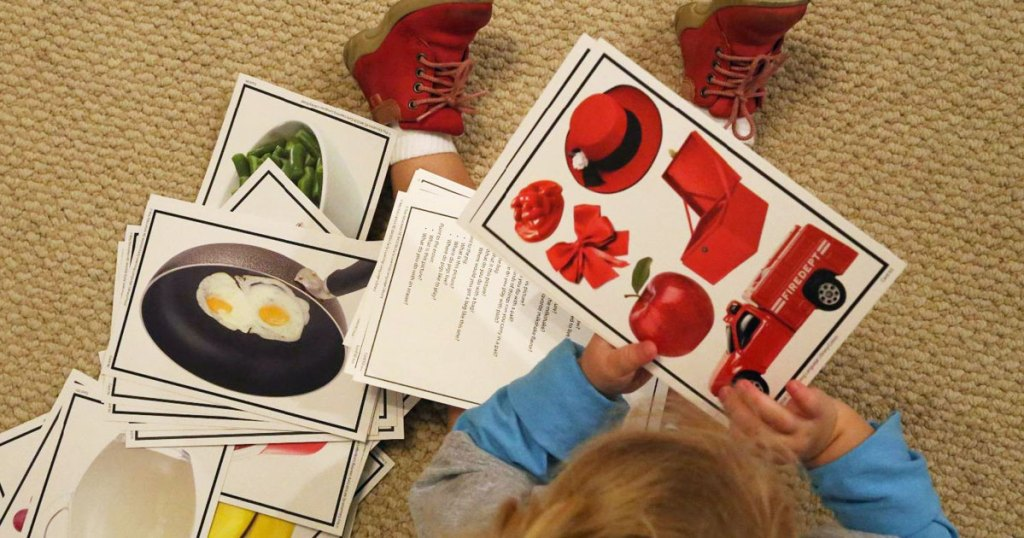 kid on floor with language cards