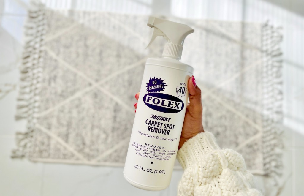 hand holding stain remover over rug