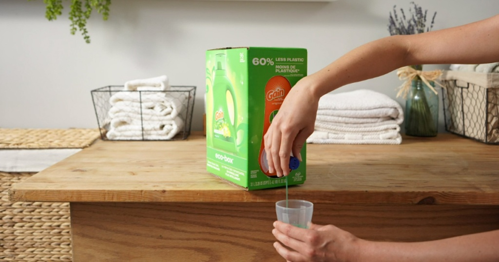 woman pouring laundry detergent from large box on counter