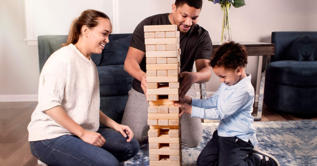 man, woman, and child sitting on a floor playing with large block tumbling tower
