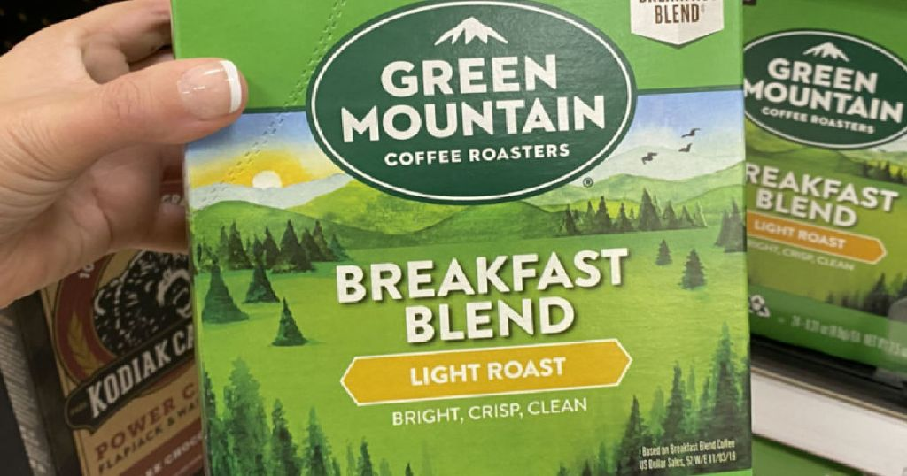 hand holding green box of coffee pods