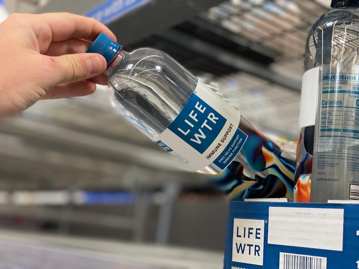 hand holding lifewtr immune support bottle off shelf