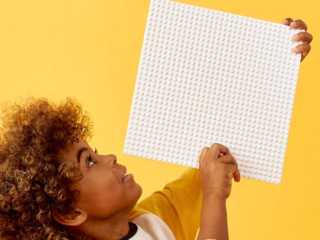child holding a white lego base plate