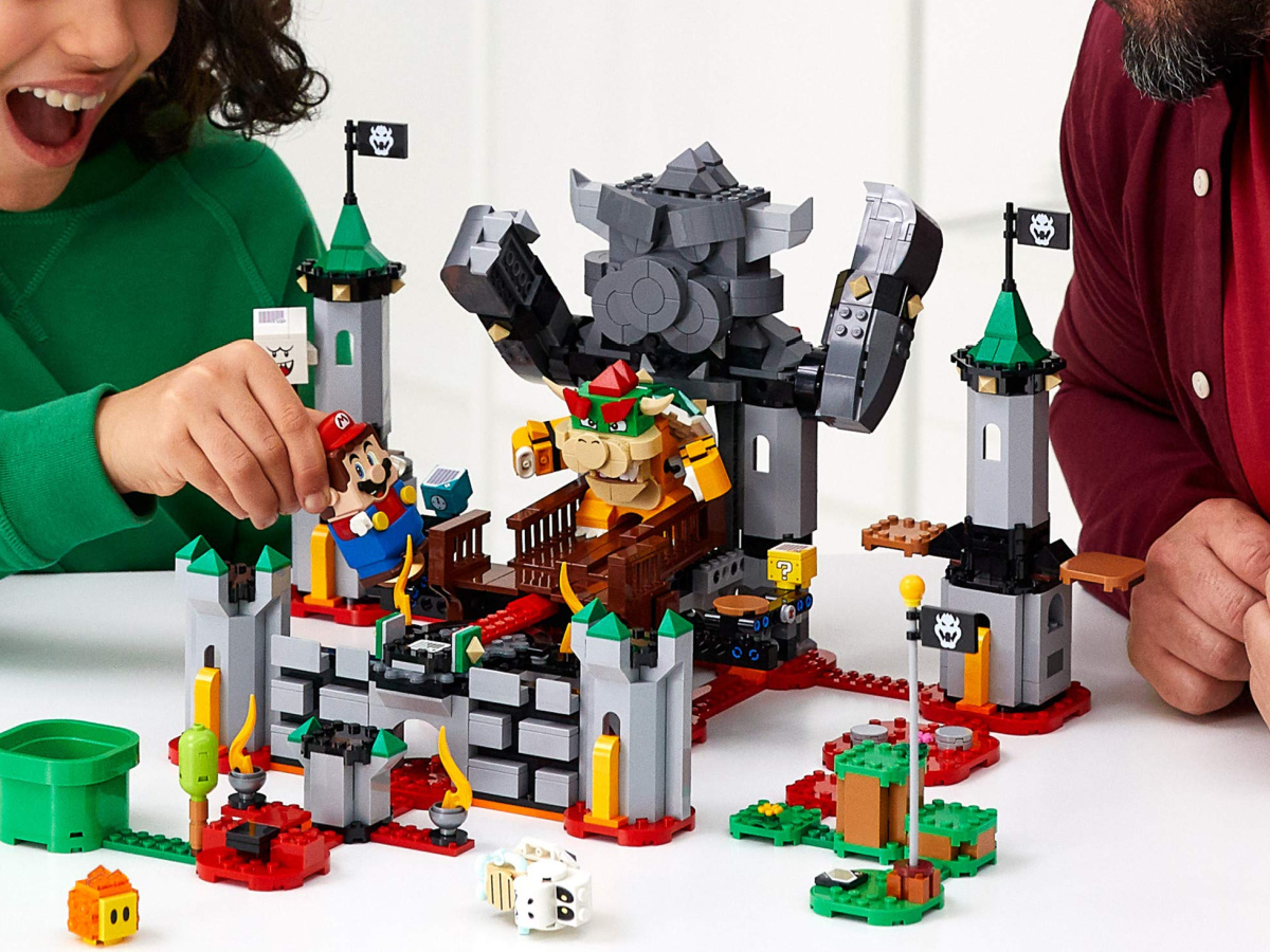 adult and child playing with a lego mario building set