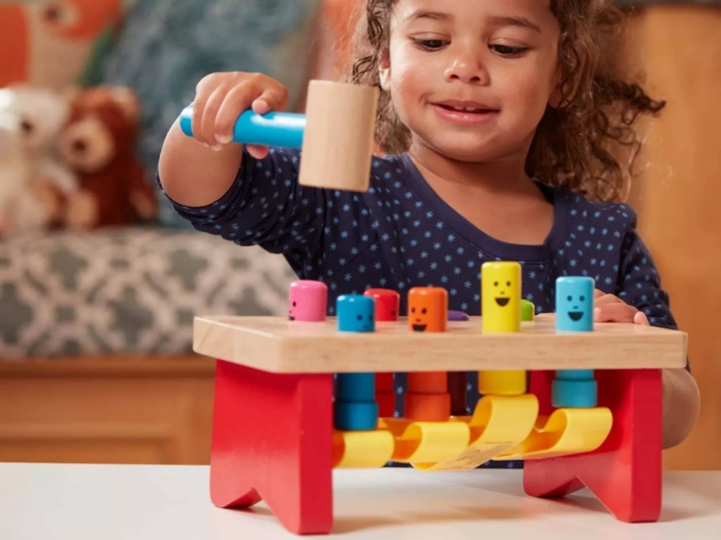 girl playing with melissa and doug wooden pound bench