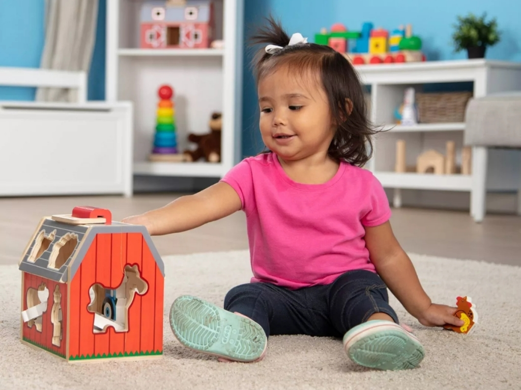 little girl playing with melissa and doug wooden barn
