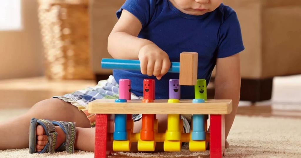 boy playing with melissa and doug wooden deluxe pound bench