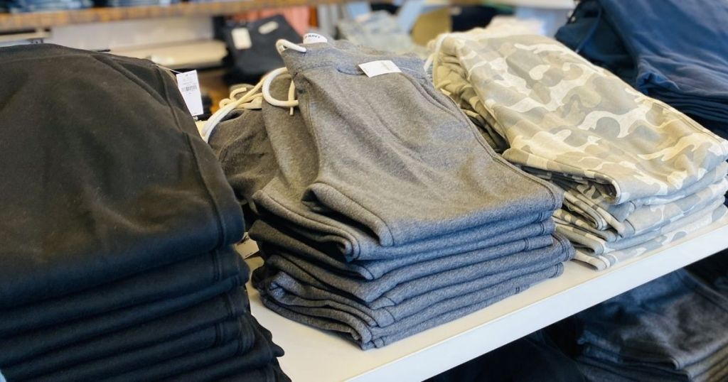 row of folded joggers on a table