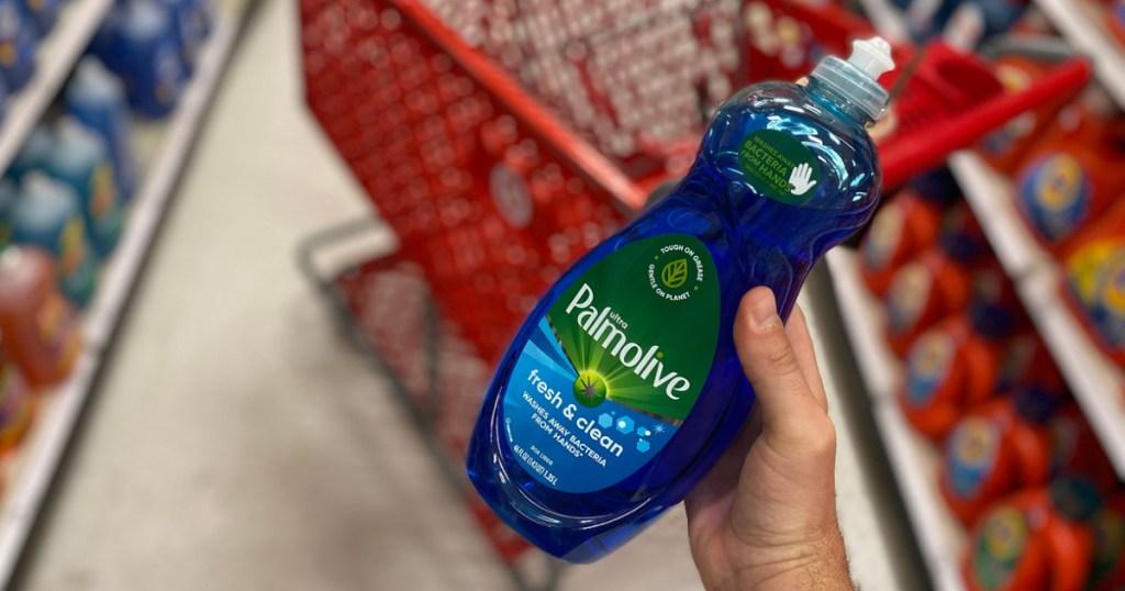 man holding a bottle of blue Palmolive dish soap