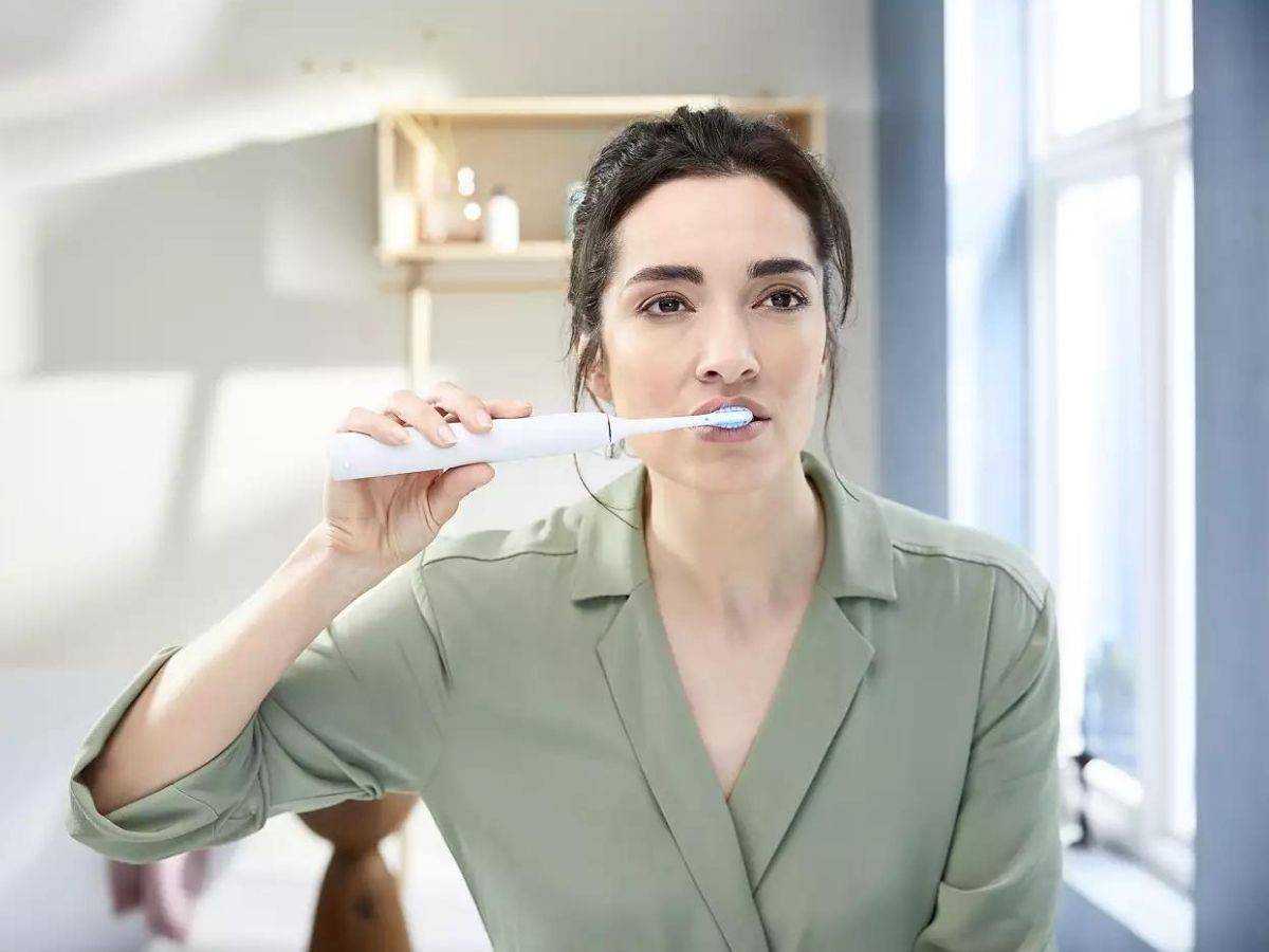 woman holding white sonicare toothbrush