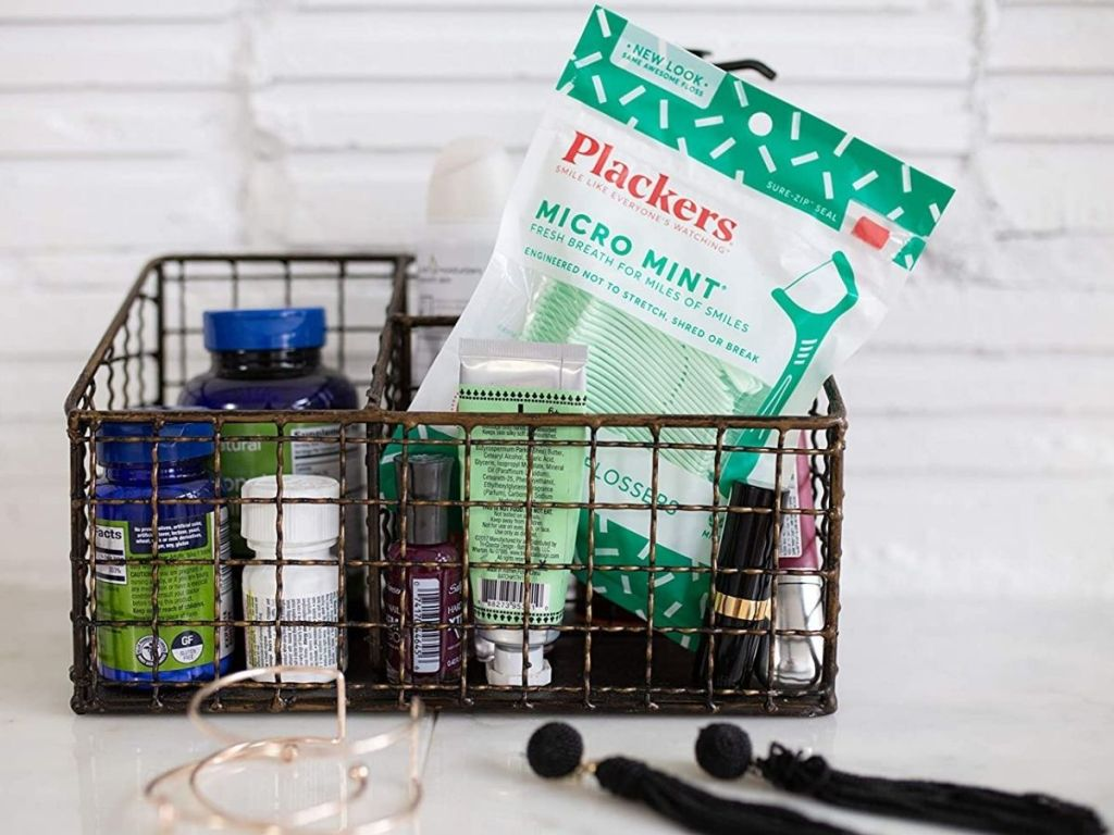 Plackers Flossers in a wire basket with other toiletires