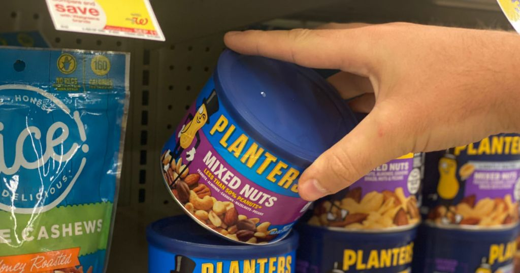 hand grabbing blue canister of nuts