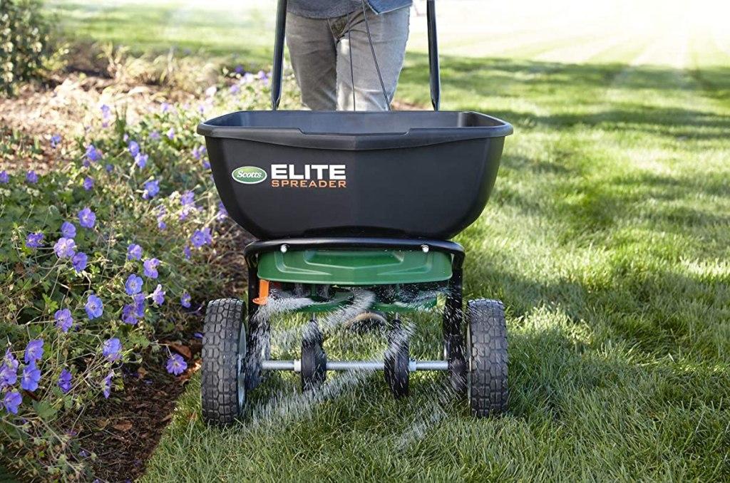 person pushing a fertilizer spreader