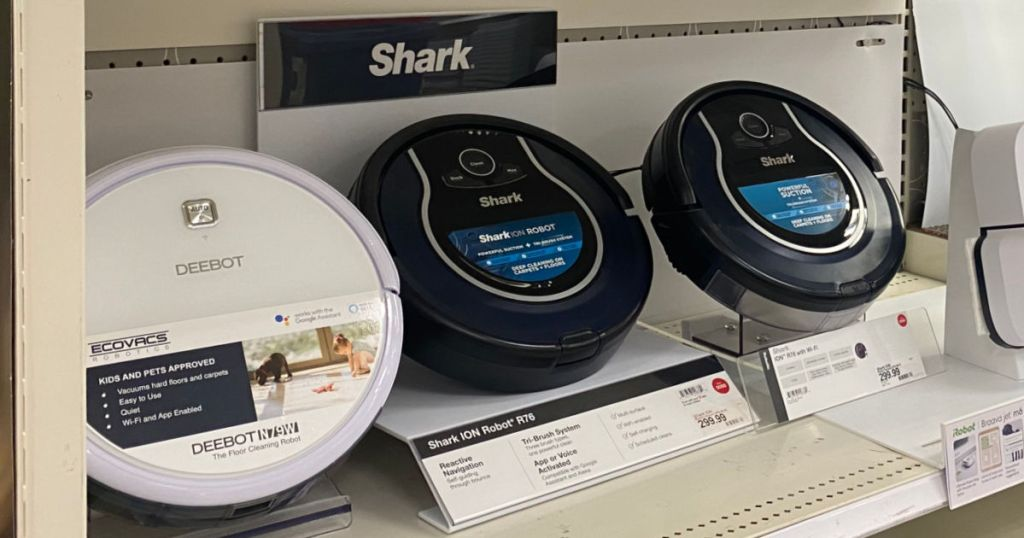two black and one white robot vacuums on shelf