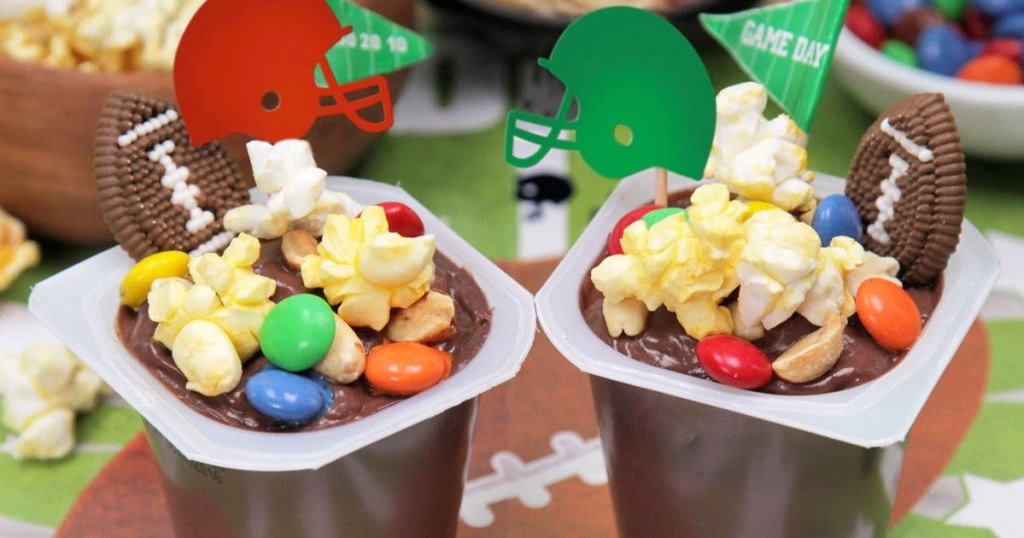 chocolate pudding cups with m&ms, popcorn, and football helmets on football themed tablecloth