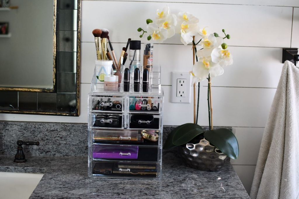 makeup organizer on a counter by a flower