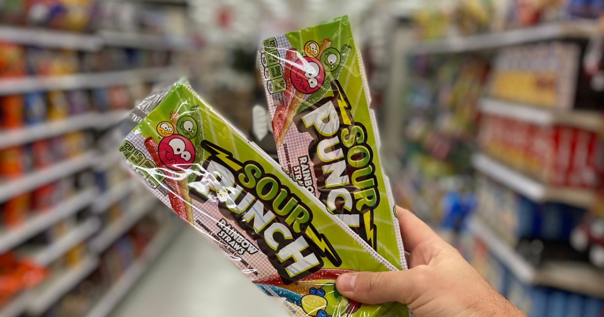 Man's hand holding two Sour Punch Straw packs