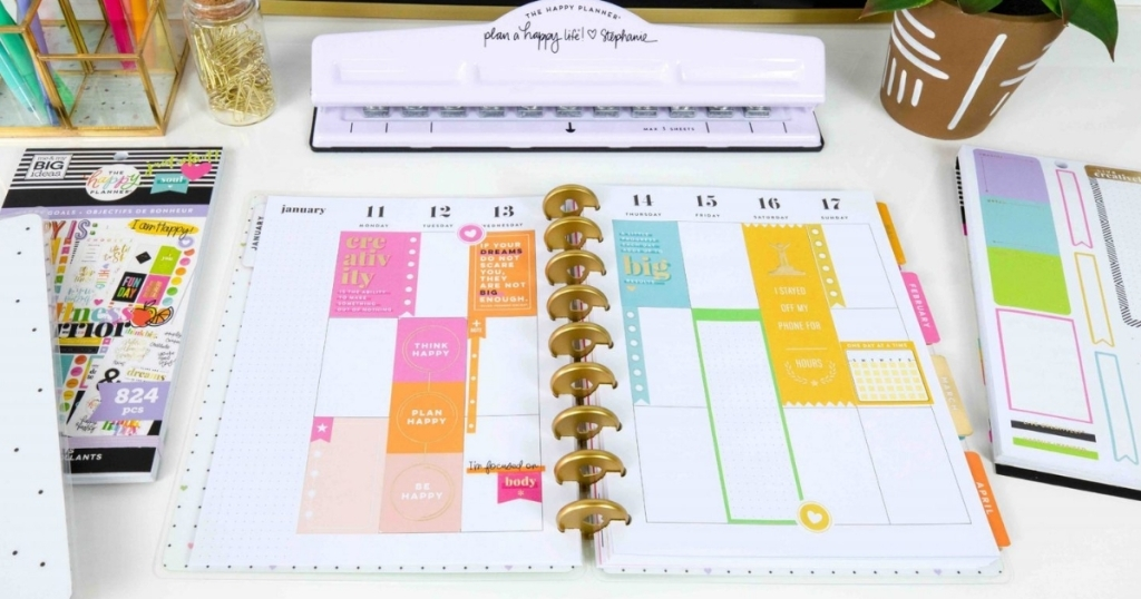 the happy planner open on table with other products