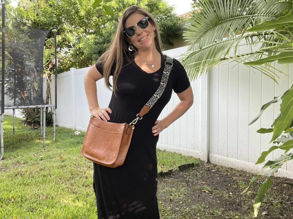 woman with a purse and sunglasses smiling at the camera