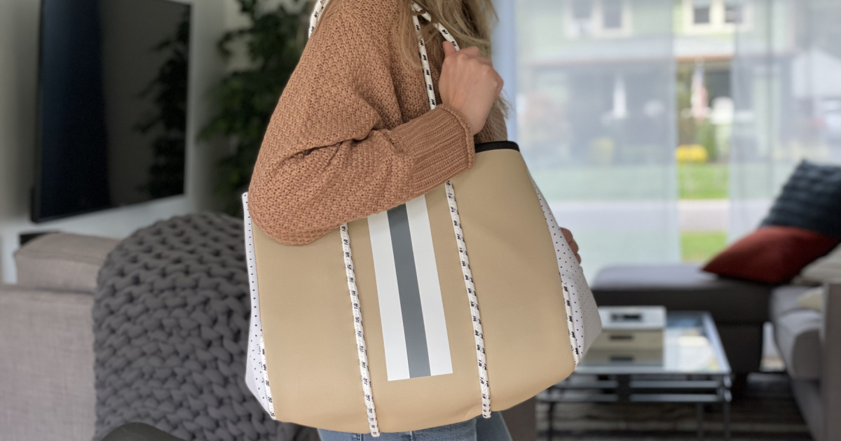 woman holding large beige purse