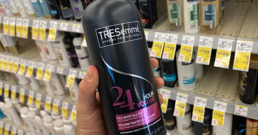 hand holding black bottle of shampoo
