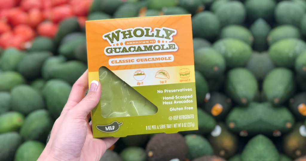 person holding package of Wholly Guacamole in a store by the avocado display