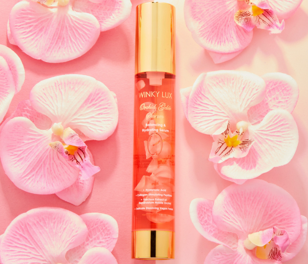 bottle of Winky Lux Orchid Gelee Serum surrounded by flower petals