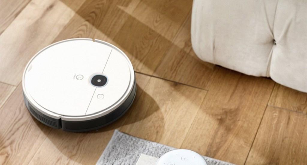 small white robotic vacuum on hardwood flooring