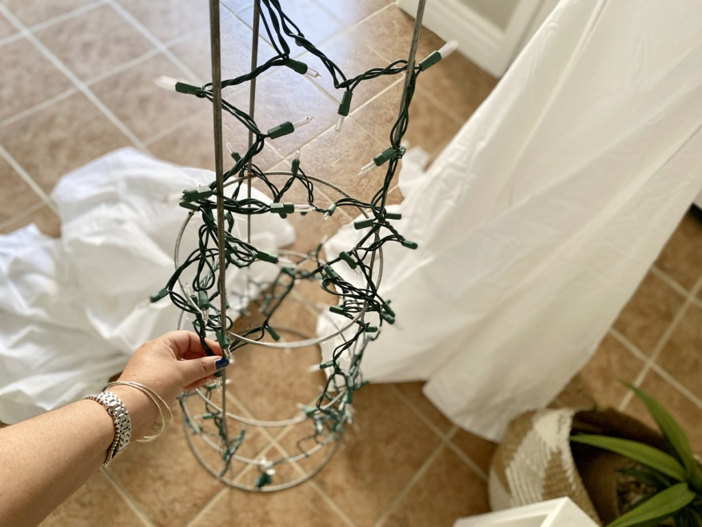adding christmas lights to a tomato cage