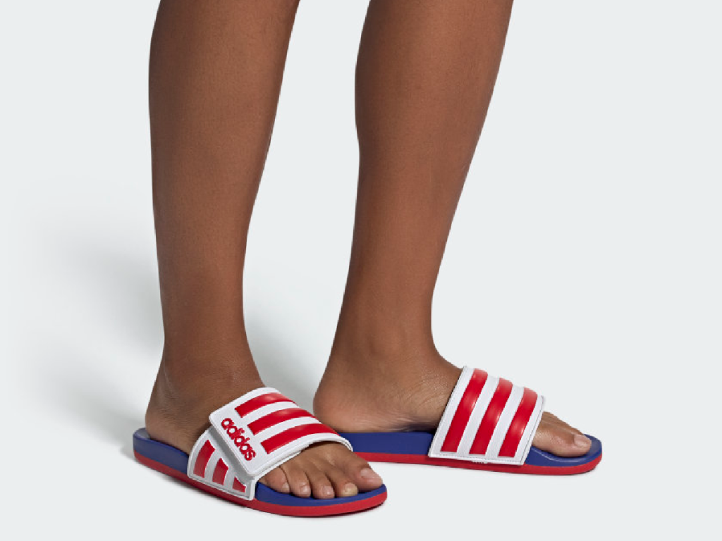 pair of legs with red white and blue sandals on their feet