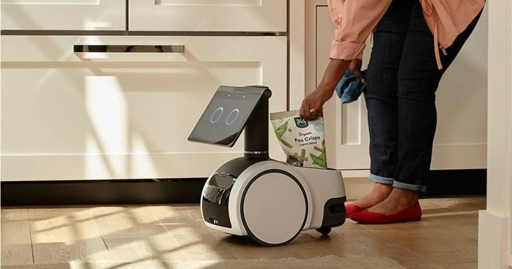 woman adding bag to household robot