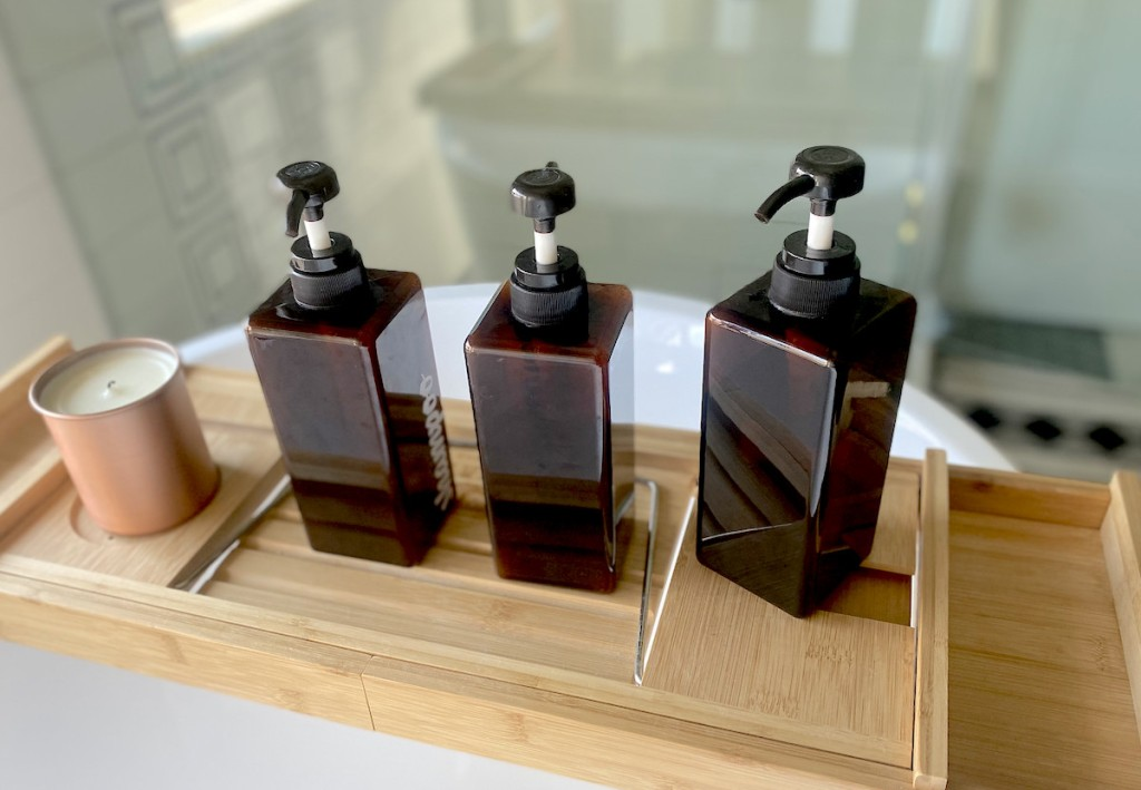 row of amber colored pump bottles on bamboo tray in bathroom - best things to buy on amazon