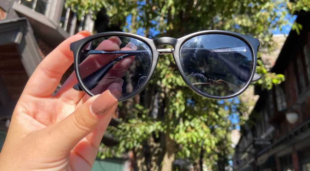hand holding a pair of black sunglasses outside in front of tree - best things to buy on amazon