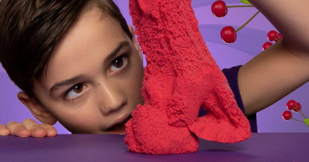 boy holding kinetic sand