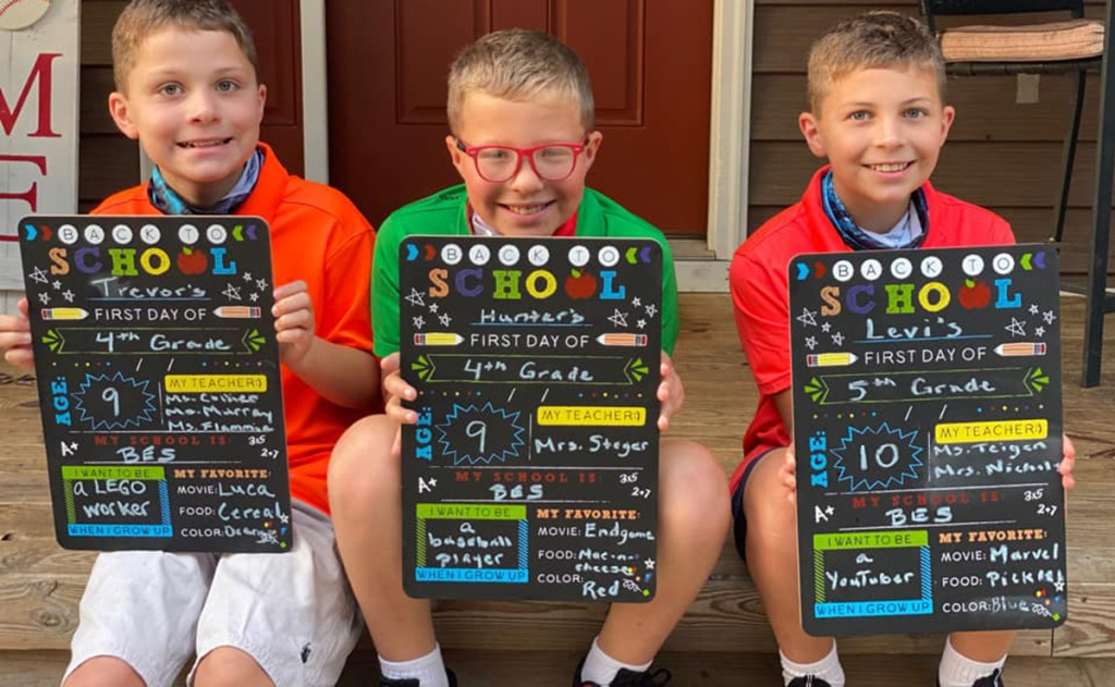 boys holding back to school sign