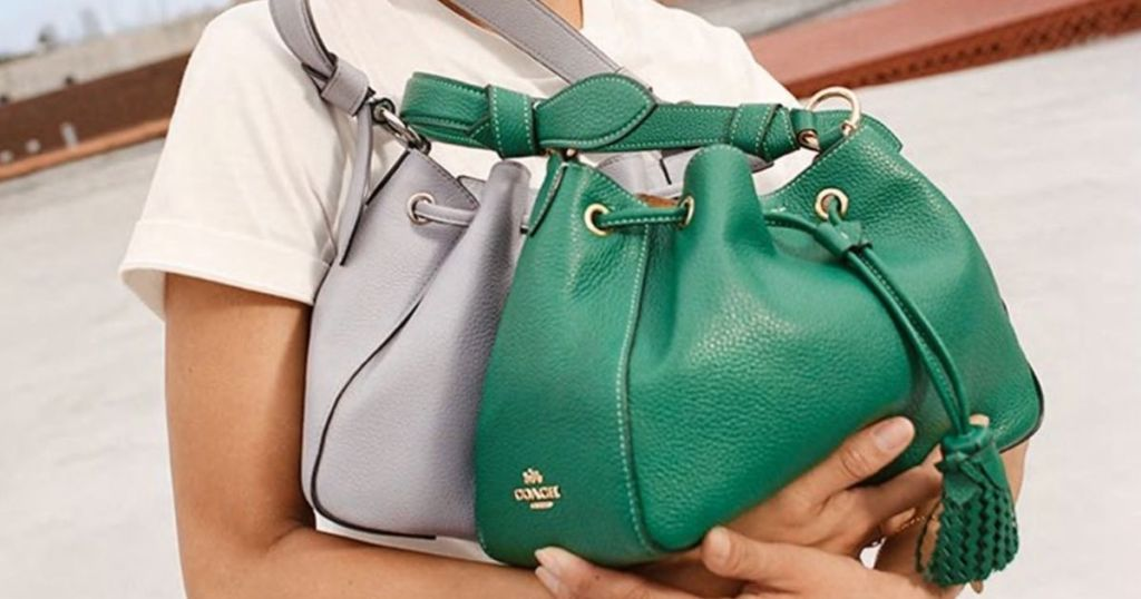 woman holding blue and green COACH bag