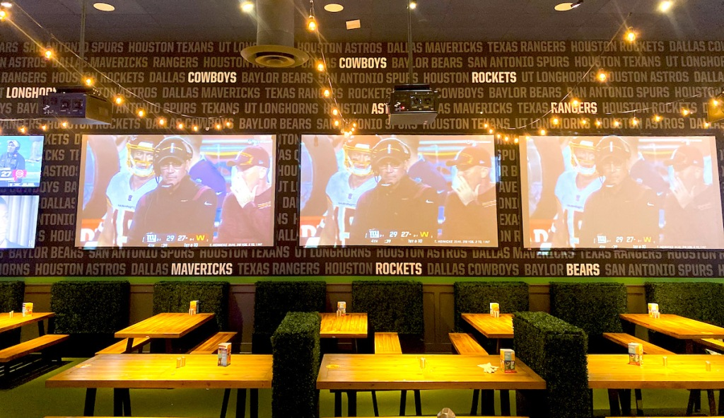 big screen tvs above picnic tables in restaurant