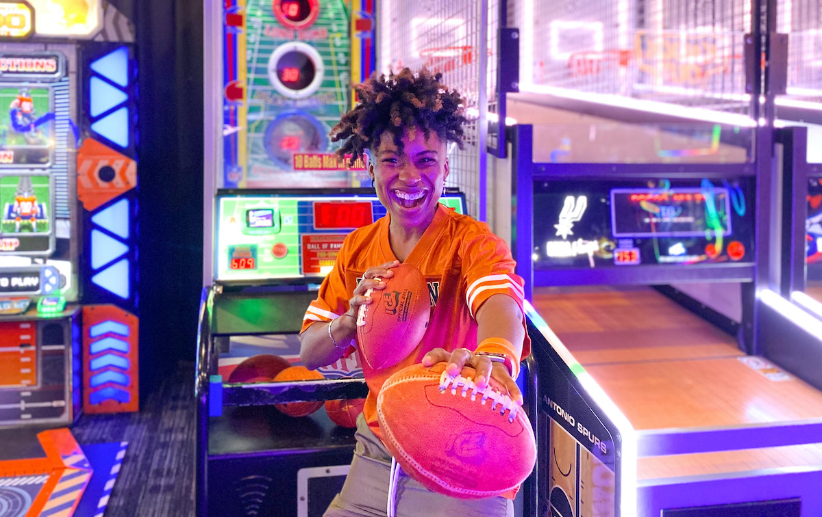 woman holding two footballs in gaming room