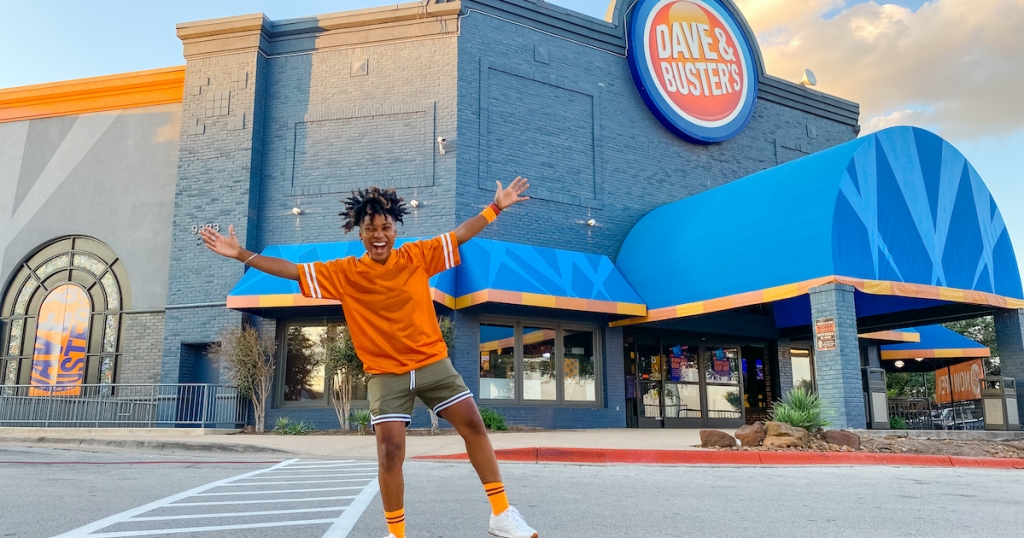 woman standing outside of dave and busters sports bar restaurant