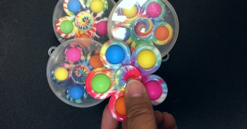 holding a pop-it fidget spinner