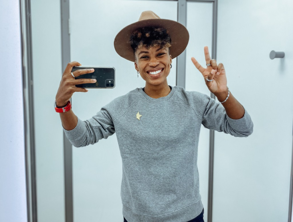 woman giving peace sign taking selfie in mirror with phone