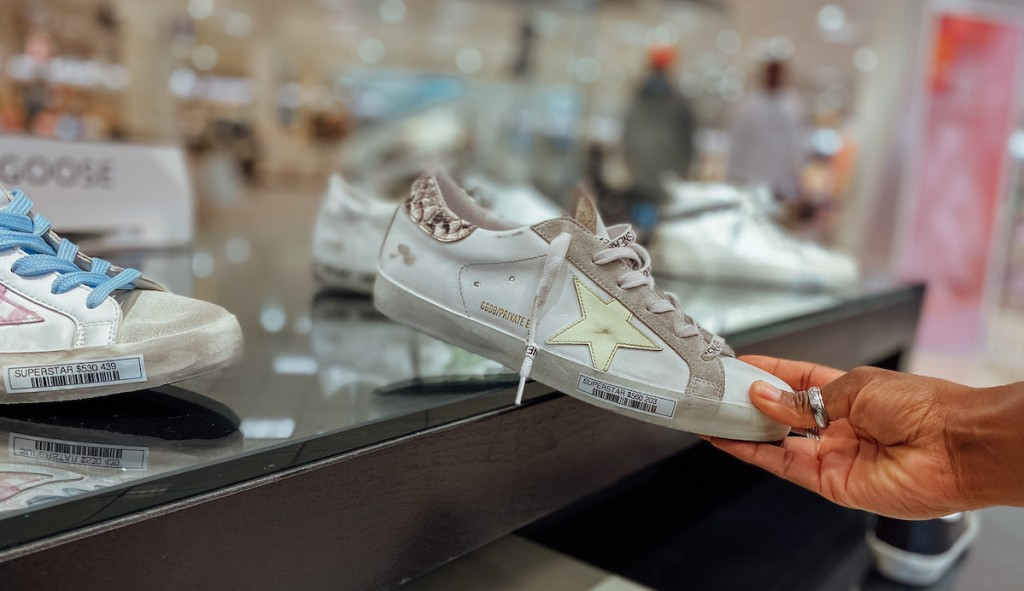 hand holding a golden goose sneaker in store