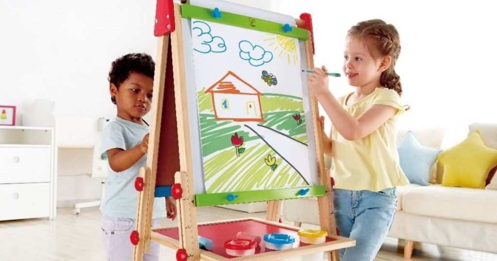 two kids drawing on an art easel
