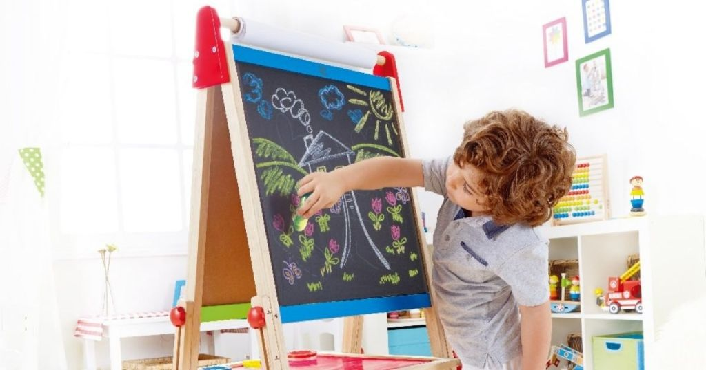 kid drawing on an art easel