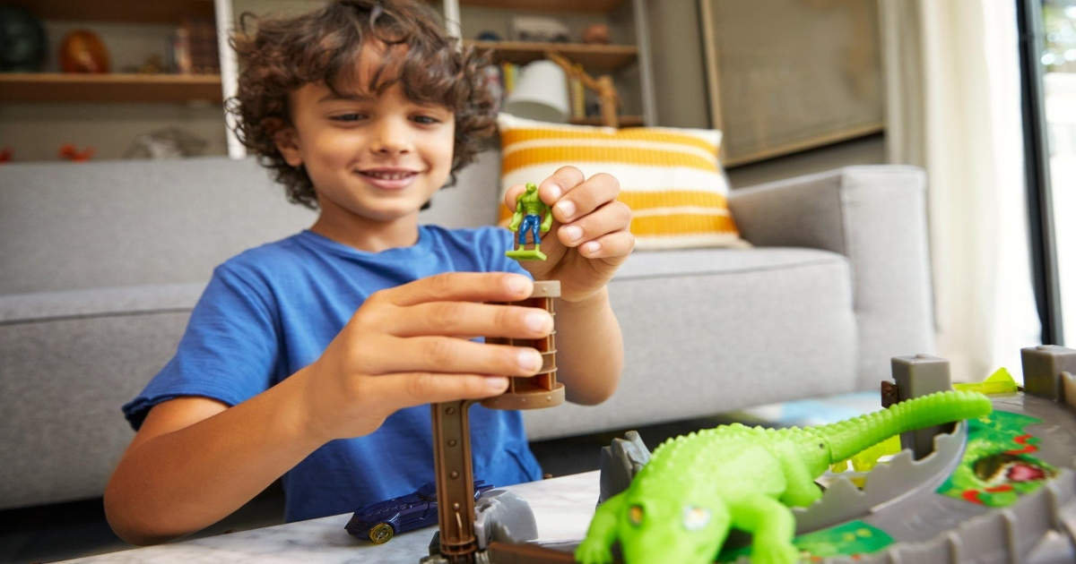 a boy playing with a Hot Wheels Escape playset